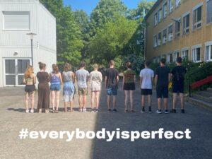 Schüler*innen stehen mit dem Rücken zur Kamera in einer Reihe, darunter #EveryBodyIsPerfect